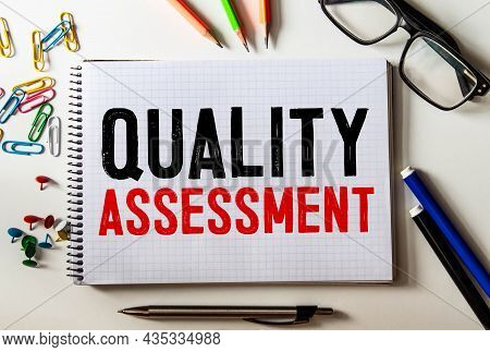 Closeup On Businessman Holding A Card With Quality Assessment Message, Business Concept Image With S