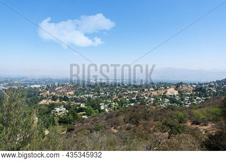 View Of Hollywood Hills Seen From Mulholland Drive On A Sunny Summer Day. Houses, Trees And Dry Patc