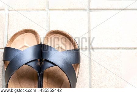 A Pair Of Slipper On Skin Of Black On Beige Tiles Background And Copy Space.