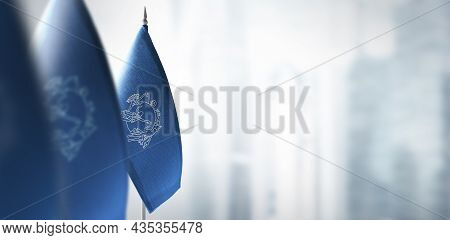 Small Flags Of Semeral Postal Union On A Blurry Background Of The City