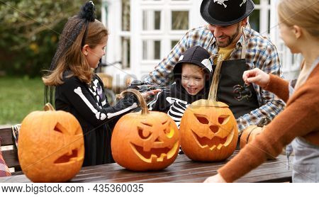 Happy Young Family In Halloween Costumes Carving Pumpkins Together In Backyard