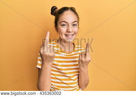 Beautiful brunette little girl wearing casual striped t shirt showing middle finger doing fuck you bad expression, provocation and rude attitude. screaming excited