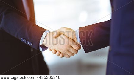 Business People Shaking Hands, Close-up. Group Of Unknown Businessmen Standing In A Sunny Modern Off