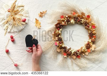 Background With Natural Fall Decorations - Dry Floral Wreath, Pampas Grass And Dry Oak Leaves. Hands