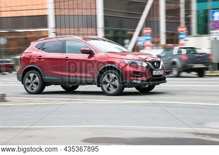 Nissan Qashqai In The City Street. Side View Of Red Crossover Car Riding On The Road On High Speed.