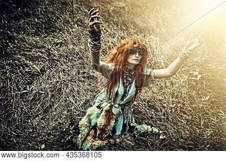 Ancient woman shaman in ritual garment and mask covering eyes standing on knees and doing an authentic ritual of summoning spirits. Paganism. Forest witch. Halloween.