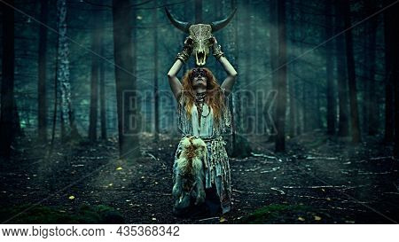 Female shaman in an ethnic dress doing a mysterious ritual holding an animal skull in her hands. Dark gloomy forest background. Black magic concept, fantasy. Paganism. Halloween.