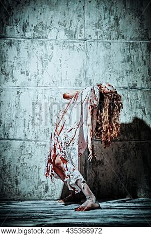 A bloody woman, possessed by the devil, bends in agony against the background of a concrete wall. Creepy zombie woman. Horror, thriller. Halloween.