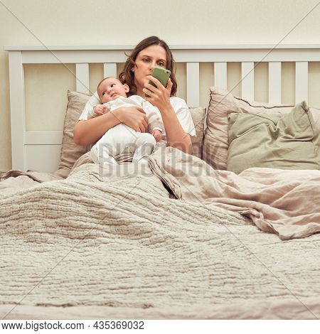 A Mother Holds A Child In Her Arms And A Mobile Phone In The Bedroom. A Lonely Woman With A Newborn