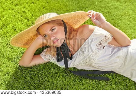 Portrait of a romantic blonde girl in an elegant white dress and wide-brimmed straw hat resting on a green lawn. Summer vacation. Summer beauty, fashion.
