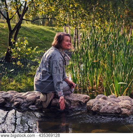 A Happy Middle-aged Woman Smiles Sitting On The Rocks By The River. An Adult Woman Enjoys Nature Sit
