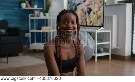 Portrait Of Fit Black Woman Looking Into Camera While Sitting In Lotus Position On Yoga Map Working