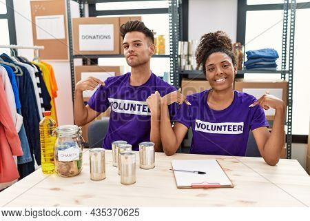 Young interracial people wearing volunteer t shirt at donations stand looking confident with smile on face, pointing oneself with fingers proud and happy.