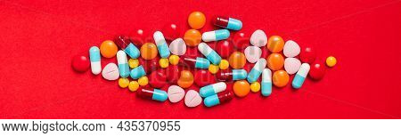 A Lot Of Pill On The Red Background. Medicine Pills, Tablets And Capsules.