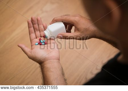 Close Up Medicine Bottle And Pills Or Capsules In Hand, Palm Or Fingers. Drug Prescription For Treat
