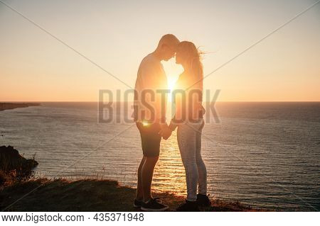 Silhouette Of A Young Romantic Couple Enjoying An Evening On A Cliff Above The Sea With A Red Burnin