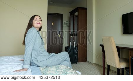 Woman In A Business Gray Suit With A Suitcase Enters The Hotel Room.