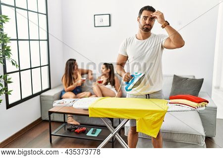 Young hispanic man ironing clothes at home worried and stressed about a problem with hand on forehead, nervous and anxious for crisis