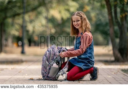 Preteen school girl with backpack sitting on the ground and smiling. Pretty pupil female kid with schoolbag in autumn park