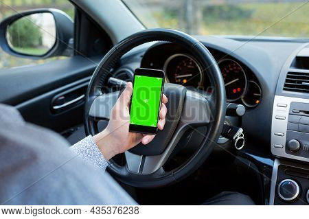 Driver's Hand Holding Smartphone With Green Screen Chroma Key Inside Car. Concept: Direction Of Trav