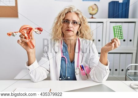 Middle age doctor woman holding birth control pills relaxed with serious expression on face. simple and natural looking at the camera.