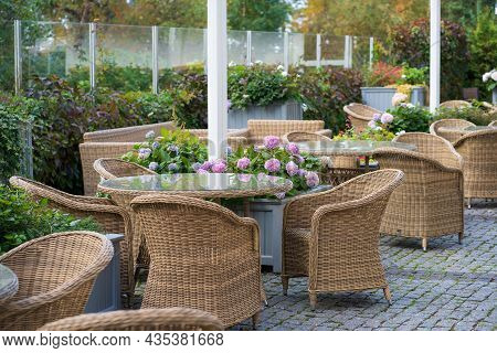 Garden Cafe Terrace Decorated With Outdoor Wicker Furniture And Growing Flowers In Pots. Empty Stree