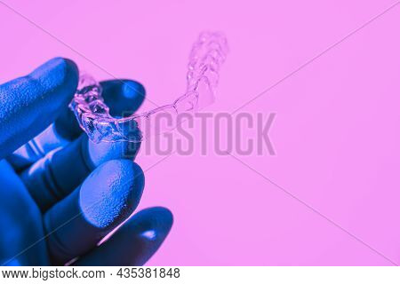 A Hand In A Blue Glove Holds Aligners To Straighten Teeth. Plastic Braces Dentistry Retainers To Str