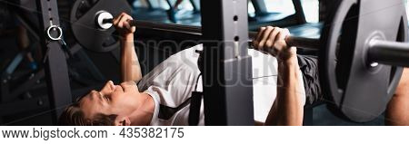 Athletic Man Working Out On Weightlifting Exercising Machine, Banner.