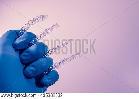Invisible Dental Braces Are Held By A Hand In A Blue Glove On A Purple Background. Plastic Braces De