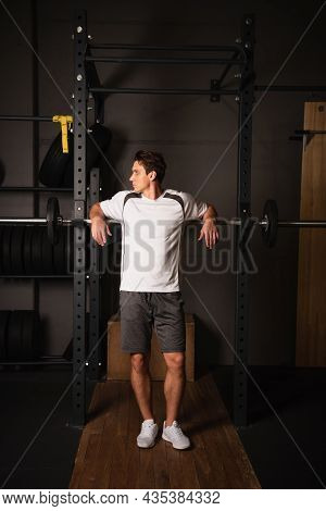 Full Length View Of Man In Sportswear Standing Near Weightlifting Exercising Machine In Gym.