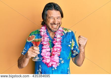 Middle age handsome man wearing hawaiian lei drinking cocktail screaming proud, celebrating victory and success very excited with raised arm