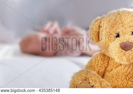 Abandoned Newborn Children Concept. Teddy Bear In Foreground. Unrecognizable Caucasian Little Child