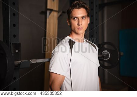 Sportive Man Looking Away While Standing Near Weightlifting Exercising Machine In Gym.