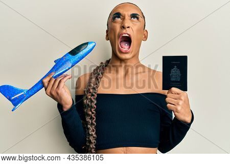Hispanic man wearing make up and long hair holding paper plane and passport angry and mad screaming frustrated and furious, shouting with anger looking up.