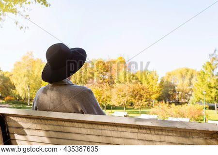 Stylish Unrecognizable Woman In Grey Coat And Black Hat With Wide Brim Sitting On Bench In Autumn Pa