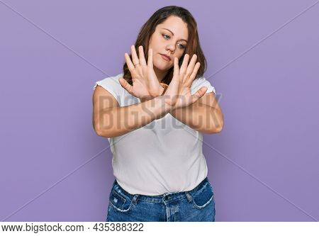 Young plus size woman wearing casual white t shirt rejection expression crossing arms doing negative sign, angry face