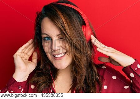 Young caucasian woman listening to music using headphones winking looking at the camera with sexy expression, cheerful and happy face.