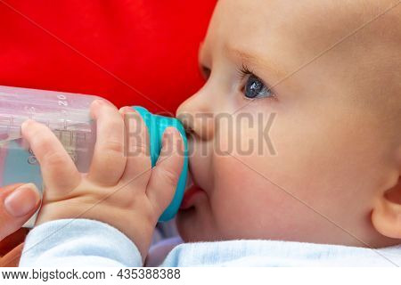Caucasian Baby Boy Eating Milk From Plastic Bottle. Focus On Blue Babys Eyes. Close Up.