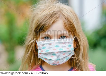Little Toddler Girl On Her First Day On Way To Playschool With Medical Mask Against Corona Covid Vir
