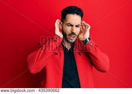 Young hispanic man wearing red leather jacket trying to hear both hands on ear gesture, curious for gossip. hearing problem, deaf