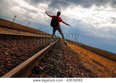 Teen girl with problems walking on rail road