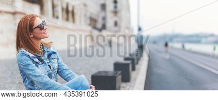 Young Cheerful Redhead Hungarian Woman Relaxing At Parliament Building, Budapest, Hungary