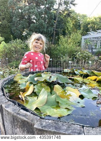 Little Preschool Girl Visiting Botanical Garden. Excited Happy Child Explore Different Flowers, Plan