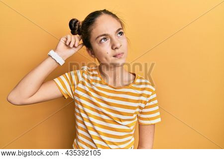 Beautiful brunette little girl wearing casual striped t shirt confuse and wondering about question. uncertain with doubt, thinking with hand on head. pensive concept.
