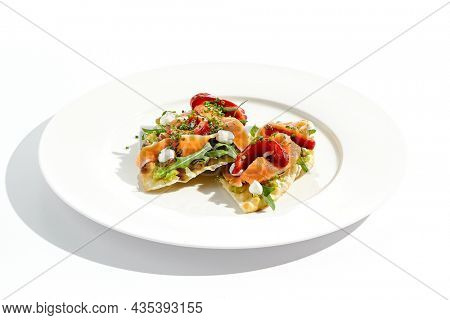 Bruschetta with salmon, avocado and paprika on white plate. Salmon bruschetta on crispy focaccia. Appetizer with guacamole, trout, cheese and paprika on toast. Fish antipasti in restaurant menu