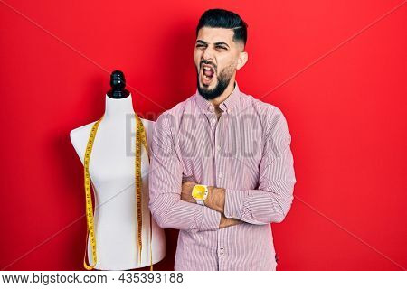 Handsome tailor man with beard with arms crossed gesture angry and mad screaming frustrated and furious, shouting with anger. rage and aggressive concept.