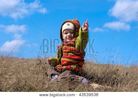 happy baby sitting on a background of the sky