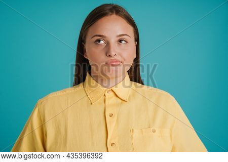 Young white woman wearing shirt grimacing and looking aside isolated over blue background