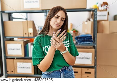 Young brunette woman wearing volunteer t shirt at donations stand suffering pain on hands and fingers, arthritis inflammation