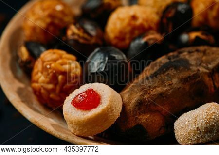 closeup of a plate with a roasted sweet potato, some roasted chestnuts and some panellets, typical confection of Catalonia, Spain, eaten traditionally in All Saints Day, in a party called Castanada